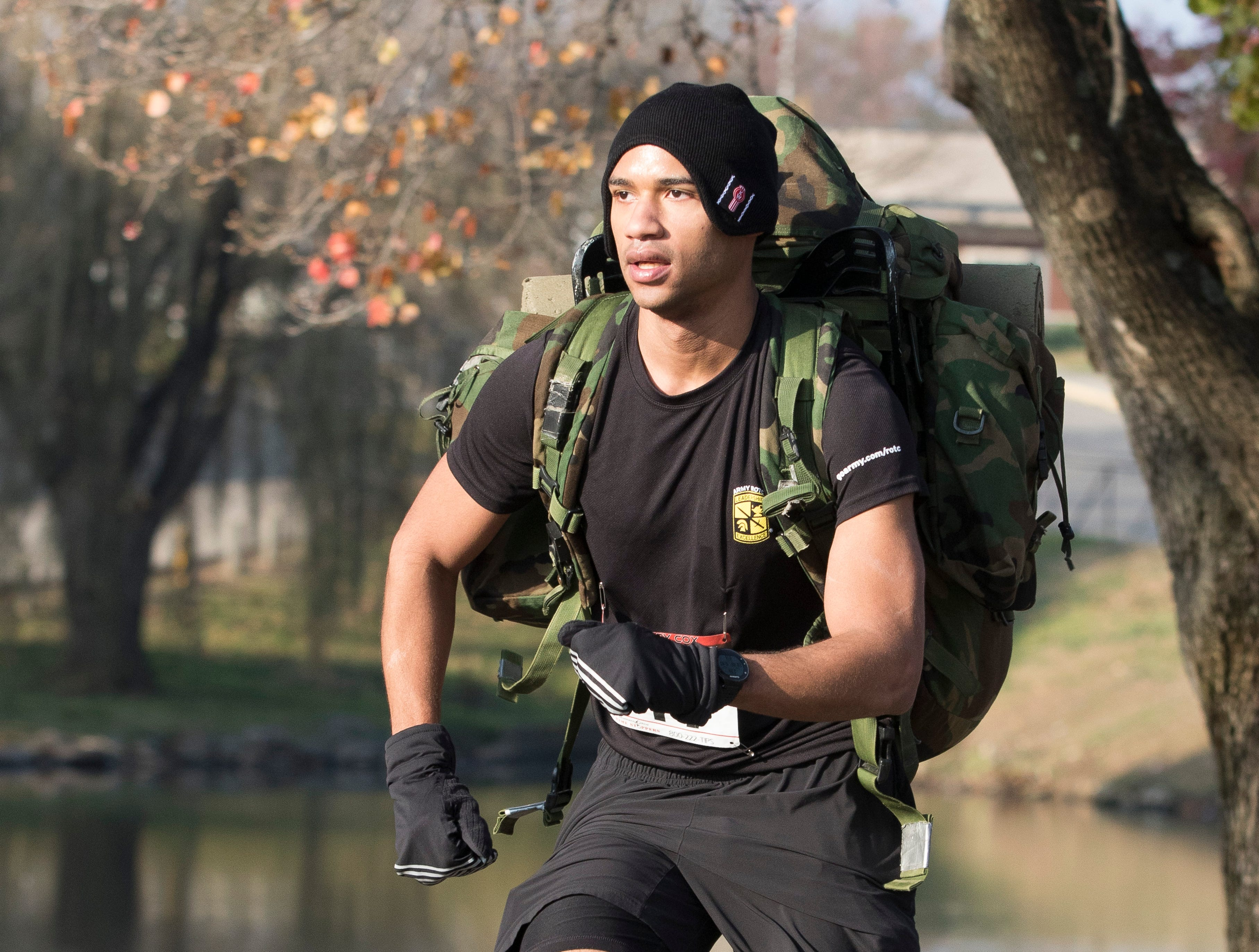 "Chillicothe native Donavan Lowe runs with his army backpack during the 14th annual Larry Cox Turkey Trot in Yoctangee Park in Chillicothe, Ohio, Thursday morning. ""I have been running for years and was like I should add my army backpack to make it more difficulty,"" said Lowe, who is currently in the Army ROTC program at St. Bonaventure University."