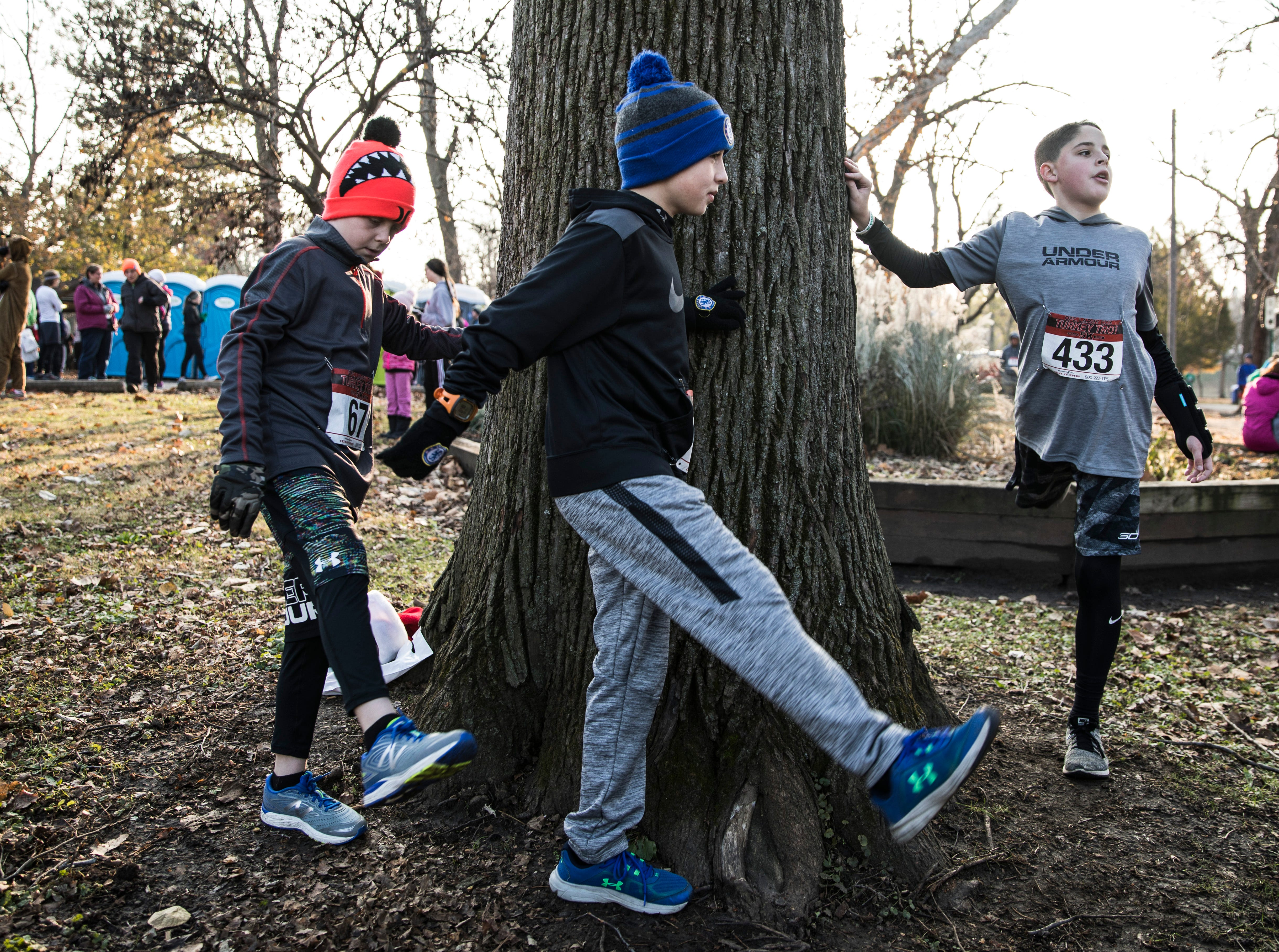 (L-R) Caleb Caplinger, Jaiden Hines, and Zeke Schobelock stretch before they run in the 14th annual Larry Cox Turkey Trot in Yoctangee Park Thursday morning in Chillicothe, Ohio.