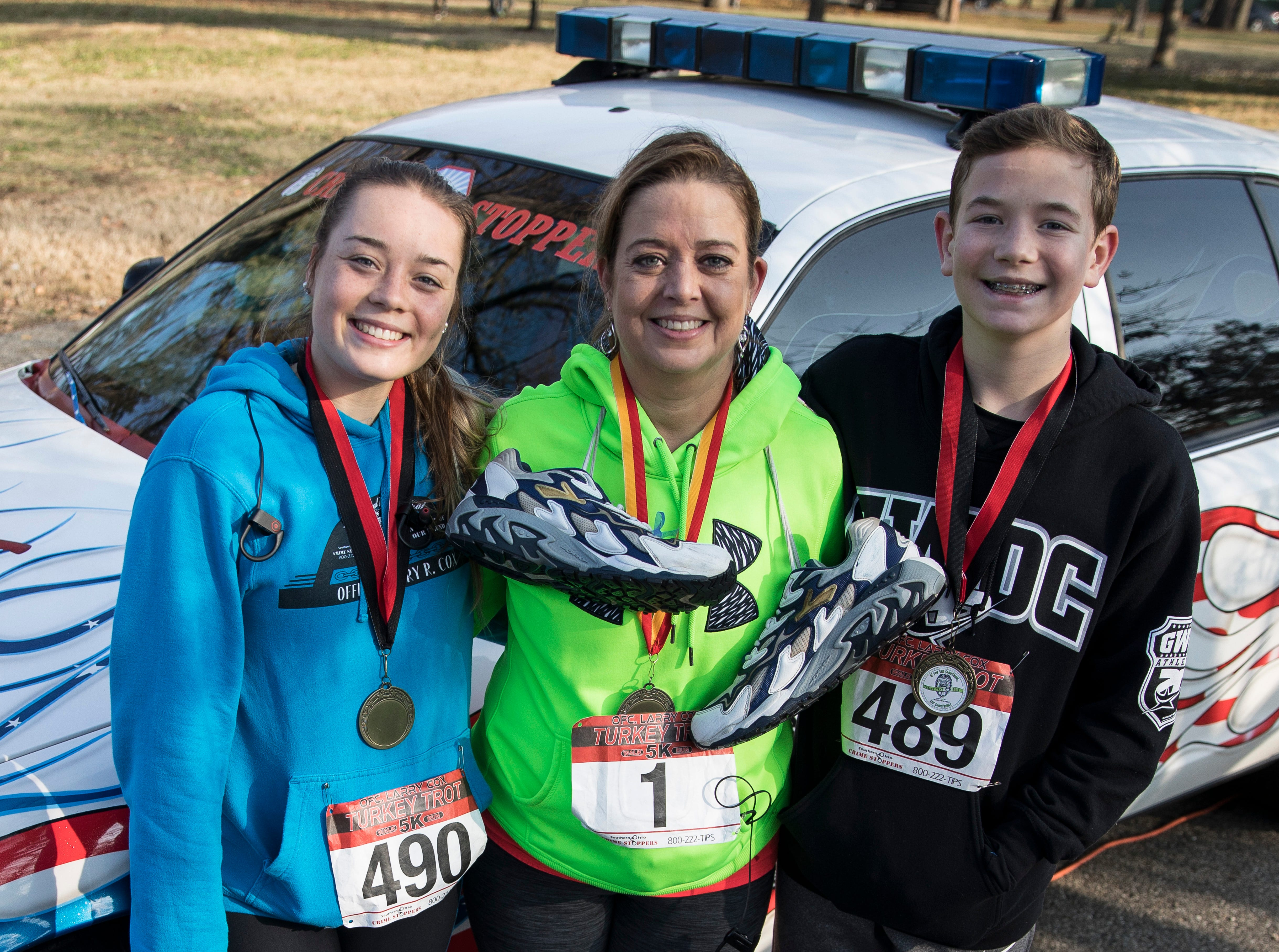 "Larry Cox's first cousin, Kelley Tamplin, center, stands with her son, Logan, and daughter, Madison, in front of the restored DARE vehicle that use to belong to former Chillicothe DARE officer Larry Cox. Each year, one person is given the honor to carry Cox's shoes as they participate in the annual Turkey Trot. The event was established as a tribute to Cox, who was a well-known runner and athlete in the community, after he was shot and killed while off duty in April 2005 while pursuing a suspect on foot. ""I started running after Larry did because I wanted to lose weight,"" said Tamplin. ""I have been waiting a long time for this and I am the only family member to carry his shoes so far."" The event raises money for Southern Ohio Crime Stoppers. For more images, go to chillicothegazette.com."