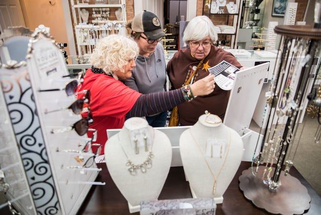 From left, Judy Ortman shows Tonya Manion and her mother in-law, Cindy Manion, the jewelry options available at Ivy's Home & Garden as they shop for the holidays in downtown Chillicothe on Black Friday.