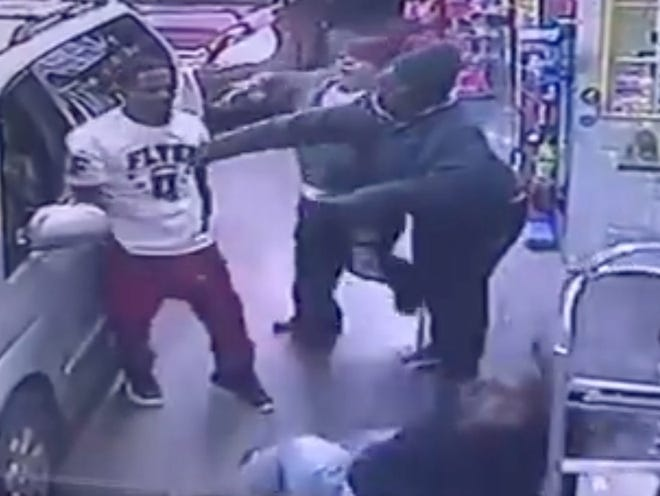 """A surveillance photo showing a man in a """"Flyer' shirt allegedly attacking a store clerk in North College Hill."""