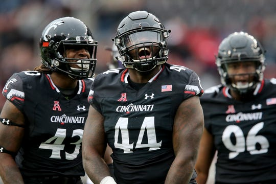 Cincinnati Bearcats defensive tackle Marquise Copeland (44), center, reacts to a sack in the first quarter of an NCAA college football game, Friday, Nov. 23, 2018, at Nippert Stadium in Cincinnati