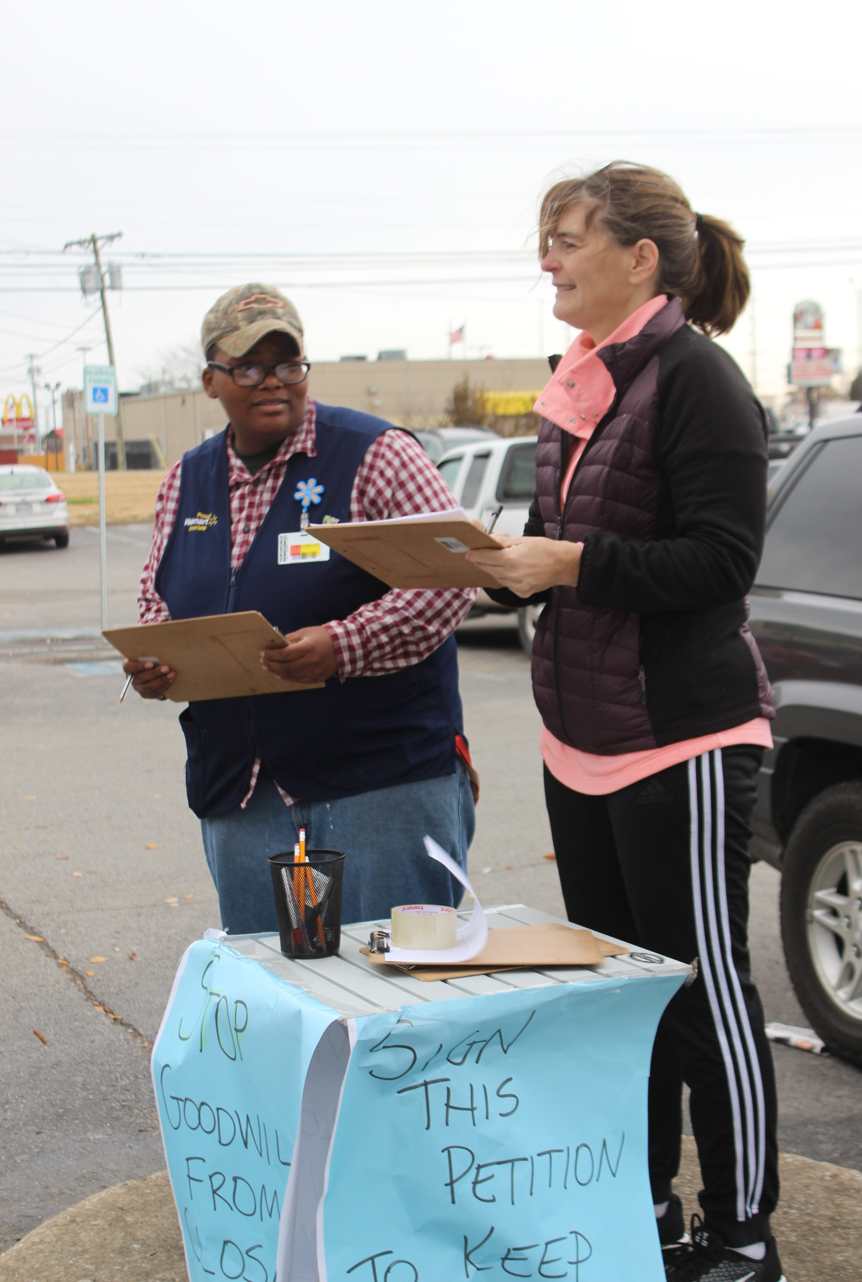 Clarksville teacher Caralee Harrison, right, stands outside the Goodwill on Fort Campbell Boulevard on Black Friday with her petition in hand in an effort to save the store.
