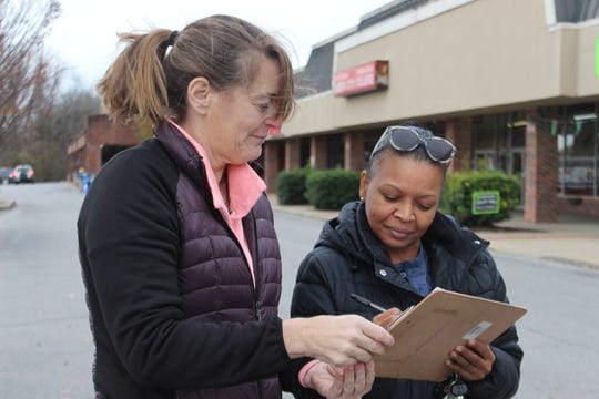 Clarksville teacher Caralee Harrison, left, gets Goodwill customer Terrell Ruskin to sign her petition to save the store on Fort Campbell Boulevard.