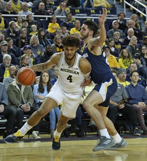 Michigan forward Isaiah Livers drives the ball to the basket as Chattanooga's Keigan Kerby defends during the first half on November 23, 2018, at Crisler Center.