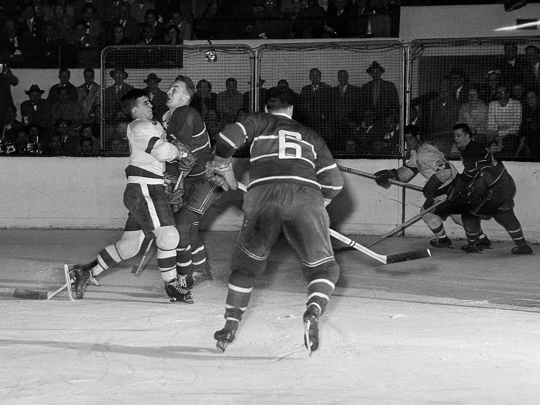 Red Wings Ted Lindsay, white shirt at left, is checked hard by Montreal defenseman Bud Macpherson who broke up this Red Wing scoring attempt in first period of Stanley Cup playoff game, March 29, 1951, Detroit.