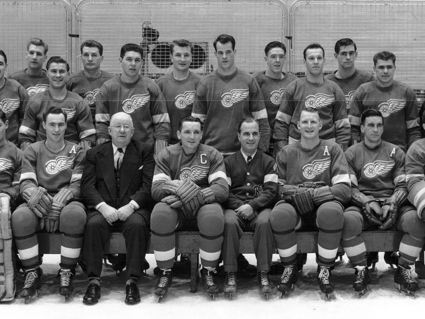 Official picture of the Detroit Red Wing squad, date unknown.  Front Row (left to right) Harry Lumley, Jack Stewart, General Manager Jack Adams, Capt. Sid Abel, Coach Tommy Ivan, Bill Quackenbush, Paul McGratton.  Middle row:  Walter Crossman, Earl Mattson, Jim Conacher, Fern Gauthier, Len Kelly, Leo Reise, Gordon Howe, Don Morrison, Ernie Burton, Trainer Frank Walker.  Top Row: Marty Pavelich, Bep Guidolin, Pete Horeck, Jim McFadden, Ted Lindsay, Rod Morrison, Seated in front Mascot Mike McGeary.
