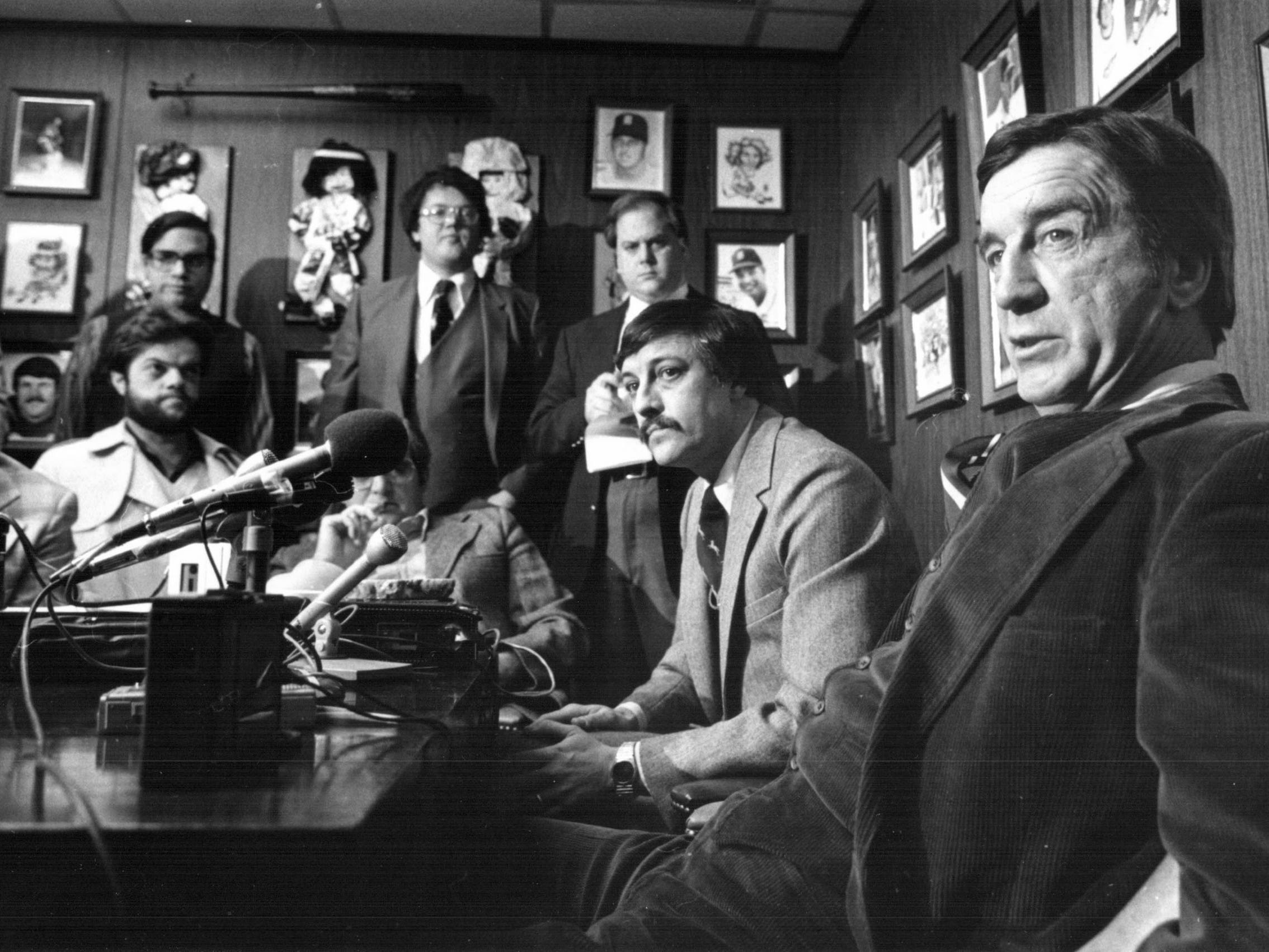 Ted Lindsay explains to reporters why he is considering a lawsuit against the Detroit Red Wings and gives his views on what it will take to turn the once-proud NHL club around during a news conference in January 1981.  Lindsay (R) is seated with his agent, Troy attorney Brian Smith in Smith's office.
