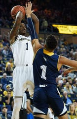 Michigan guard Charles Matthews shoots over Chattanooga guard Jonathan Scott in the first half of U-M's 83-55 win on Friday, Nov. 23, 2018, at Crisler Center.
