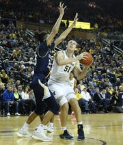 Michigan center Austin Davis drives the ball to the basket as Cahattanooga's Justin Brown defends during the first half of U-M's 83-55 win on Friday, Nov. 23, 2018, at Crisler Center.