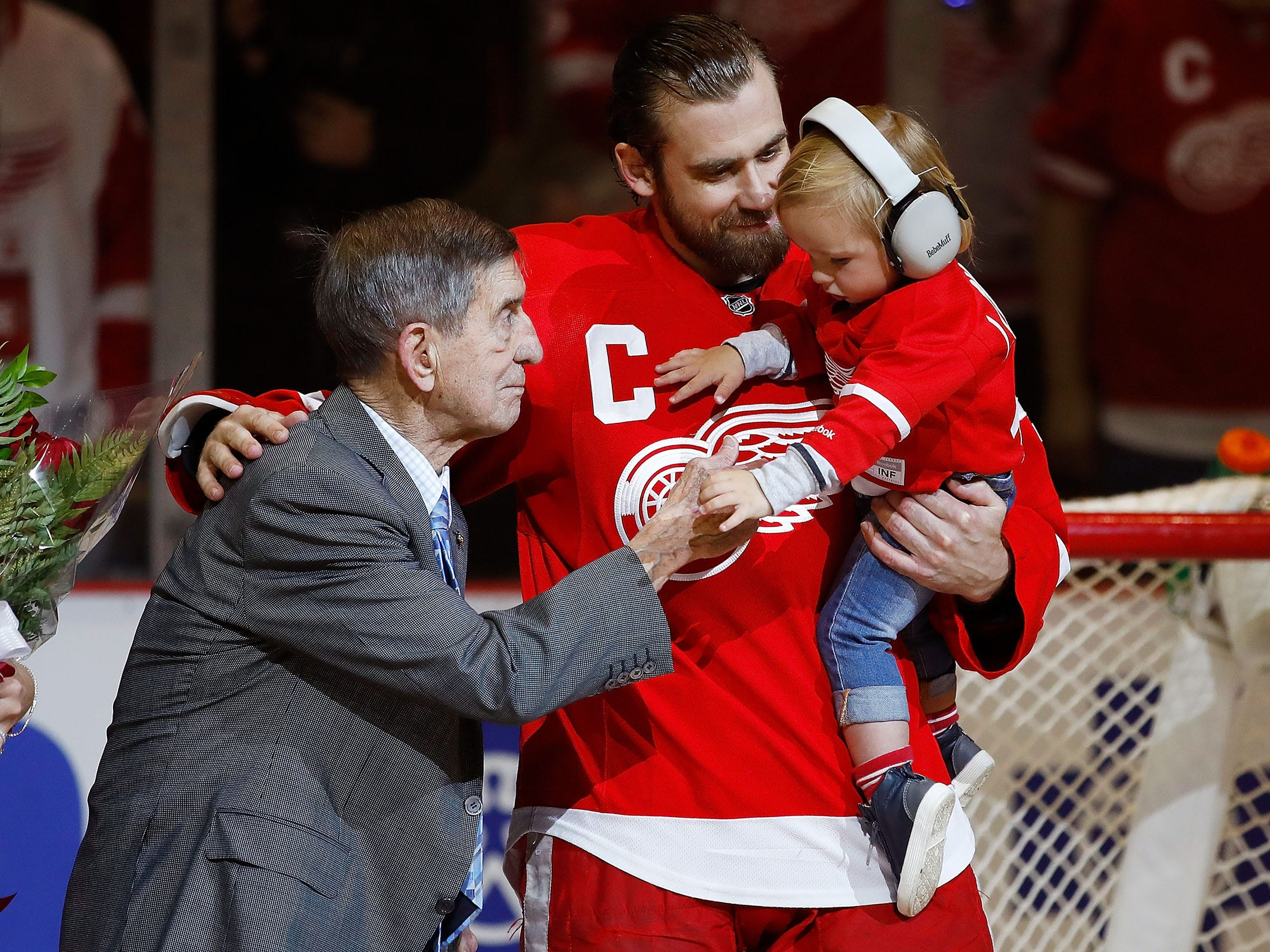 Henrik Zetterberg of the Red Wings, his son Love and Red Wings legend Ted Lindsay during presentation to honor his 1000th NHL game prior to a game against the New Jersey Devils at Joe Louis Arena on April 9, 2017 in Detroit.