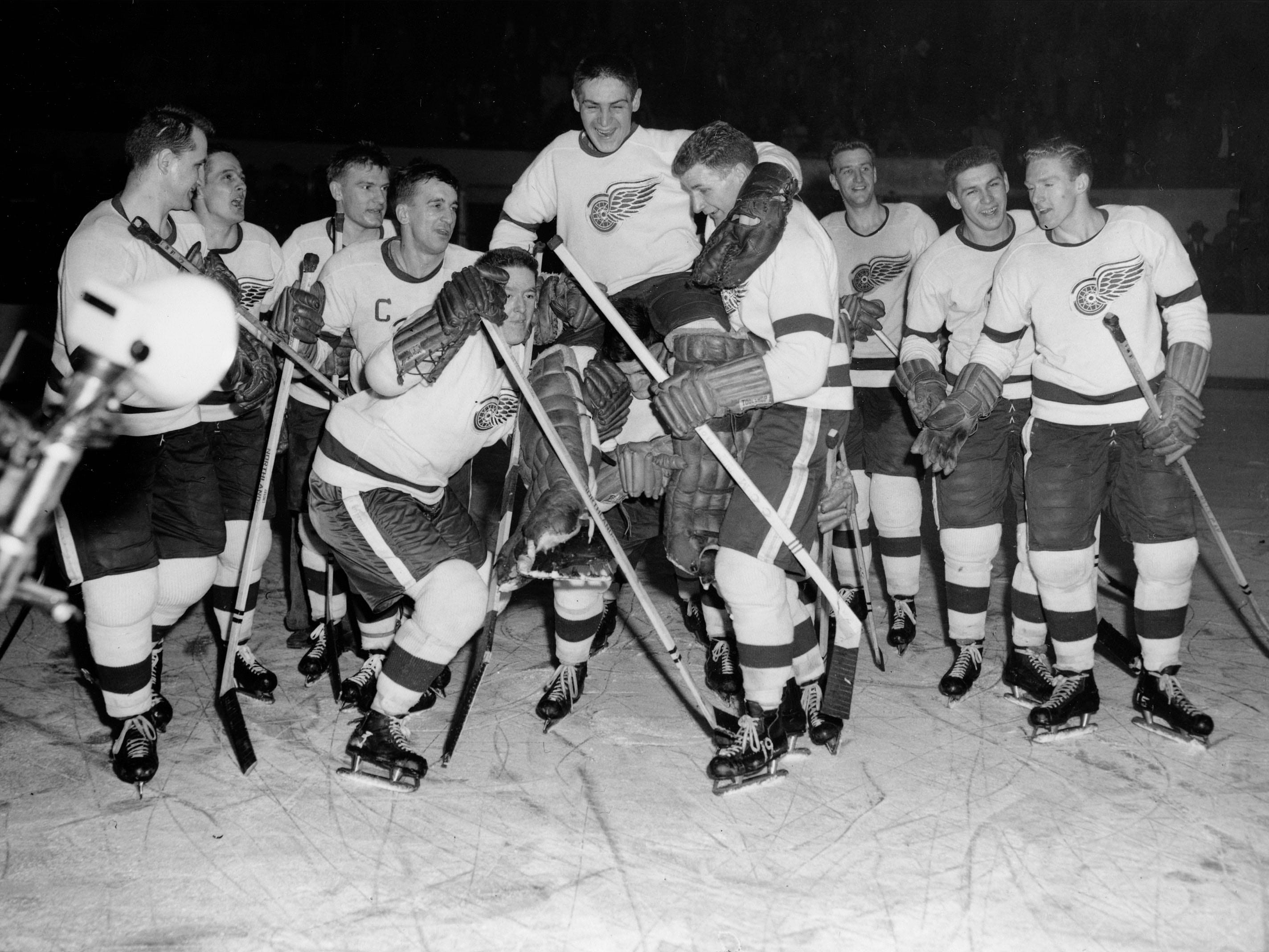 Goalie Terry Sawchuck is lifted by teammates Vic Stasiuk, right, and Marcel Pronovost after he shut out the Montreal Canadiens 6-0 to give the Detroit Red Wings the NHL championship in Detroit, March 21, 1955. Star of the game is Ted Lindsay, second from left, with three goals.