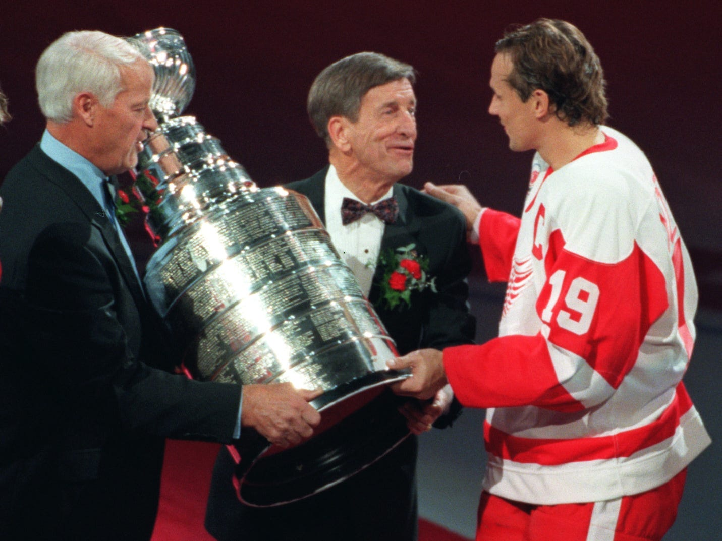 Red Wings Gordie Howe, left and Ted Lindsay present the Stanley Cup to Steve Yzerman during the pregame ceremony in October 1997.