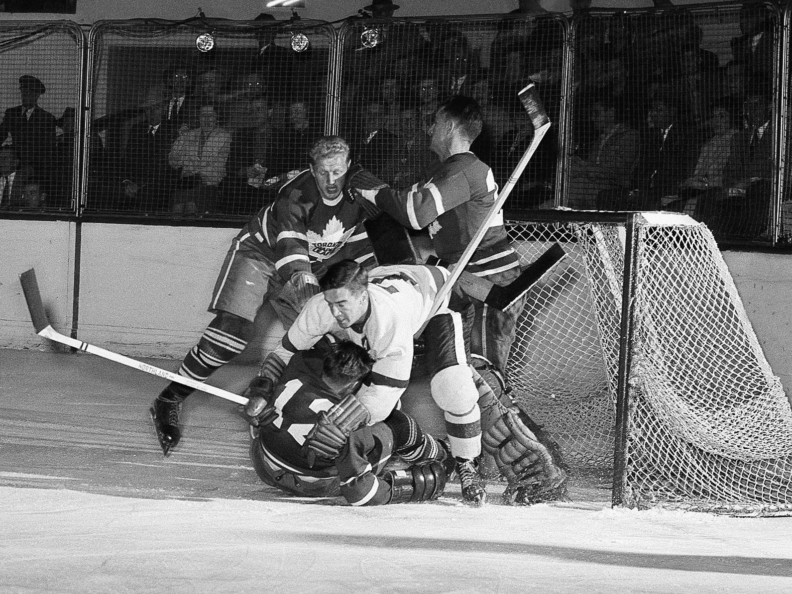 Ted Lindsay, Red Wings left wing attempts a goal in the first period of a game between the Detroit Red Wings and Toronto Maple Leafs, Oct. 14, 1951, Detroit. On the play Lindsay, white shirt no. 7, beneath him is Leafs Fernie Flaman (12) and Goalie is Al Rollins.