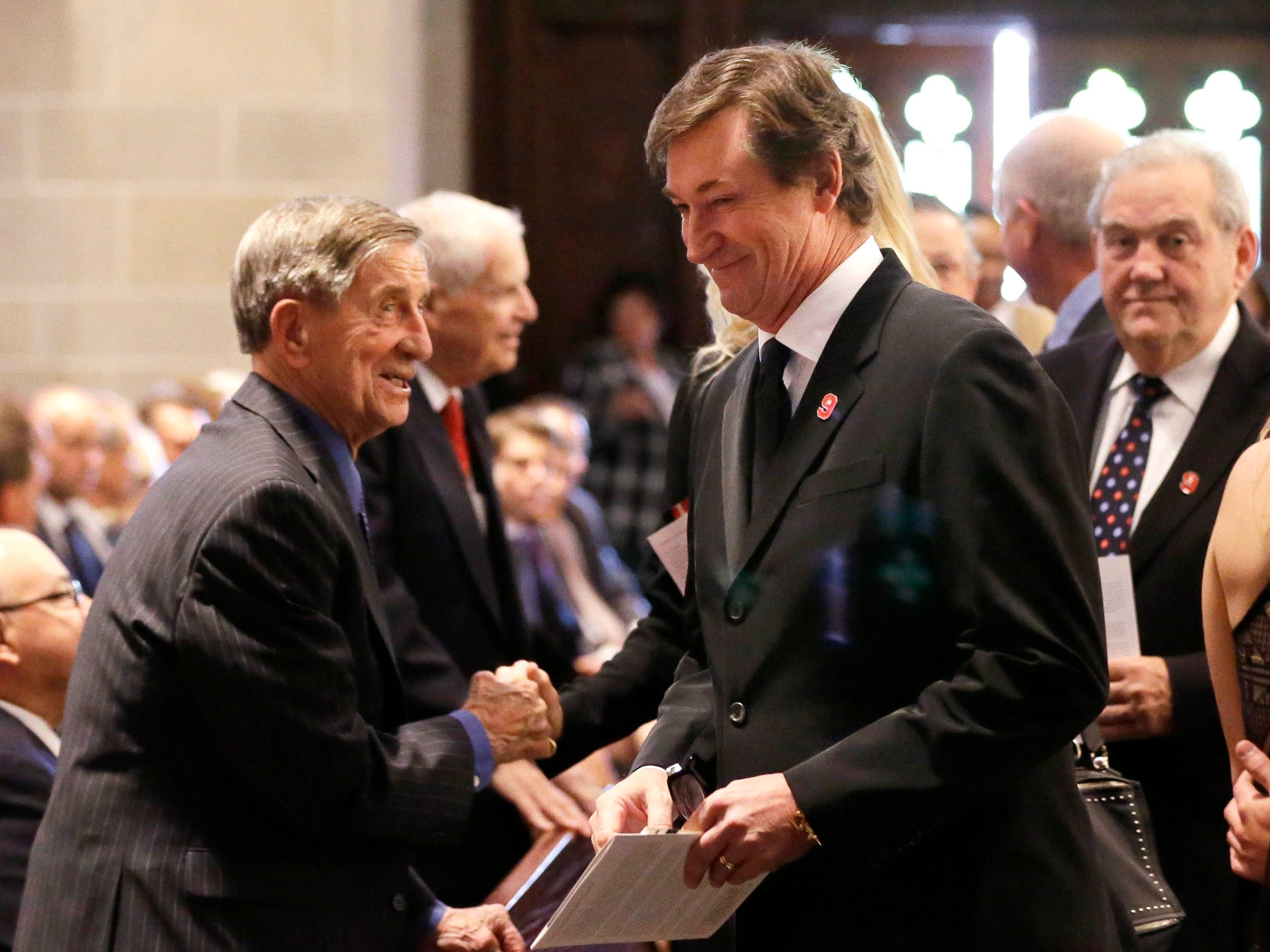 Ted Lindsay, left, greets Wayne Gretzky at the Cathedral of the Most Blessed Sacrament before the funeral for hockey legend Gordie Howe, Wednesday, June 15, 2016 in Detroit.