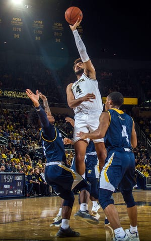 Michigan forward Isaiah Livers attempts to shoot while defended by Chattanooga guards Donovann Toatley, left, and Maurice Commander, right, in the first half at Crisler Center on Friday, Nov. 23, 2018.