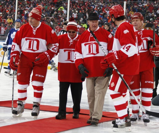 Red Wing great Gordie Howe  and Ted Lindsay (center) leave center ice with Mickey Redmond and Brendan Shanahan after dropping  the ceremonial puck to start the second game during the Alumni Showdown between the Red Wings and Toronto  Maple Leafs at Comerica Park in Detroit on Tuesday, December 31, 2013.