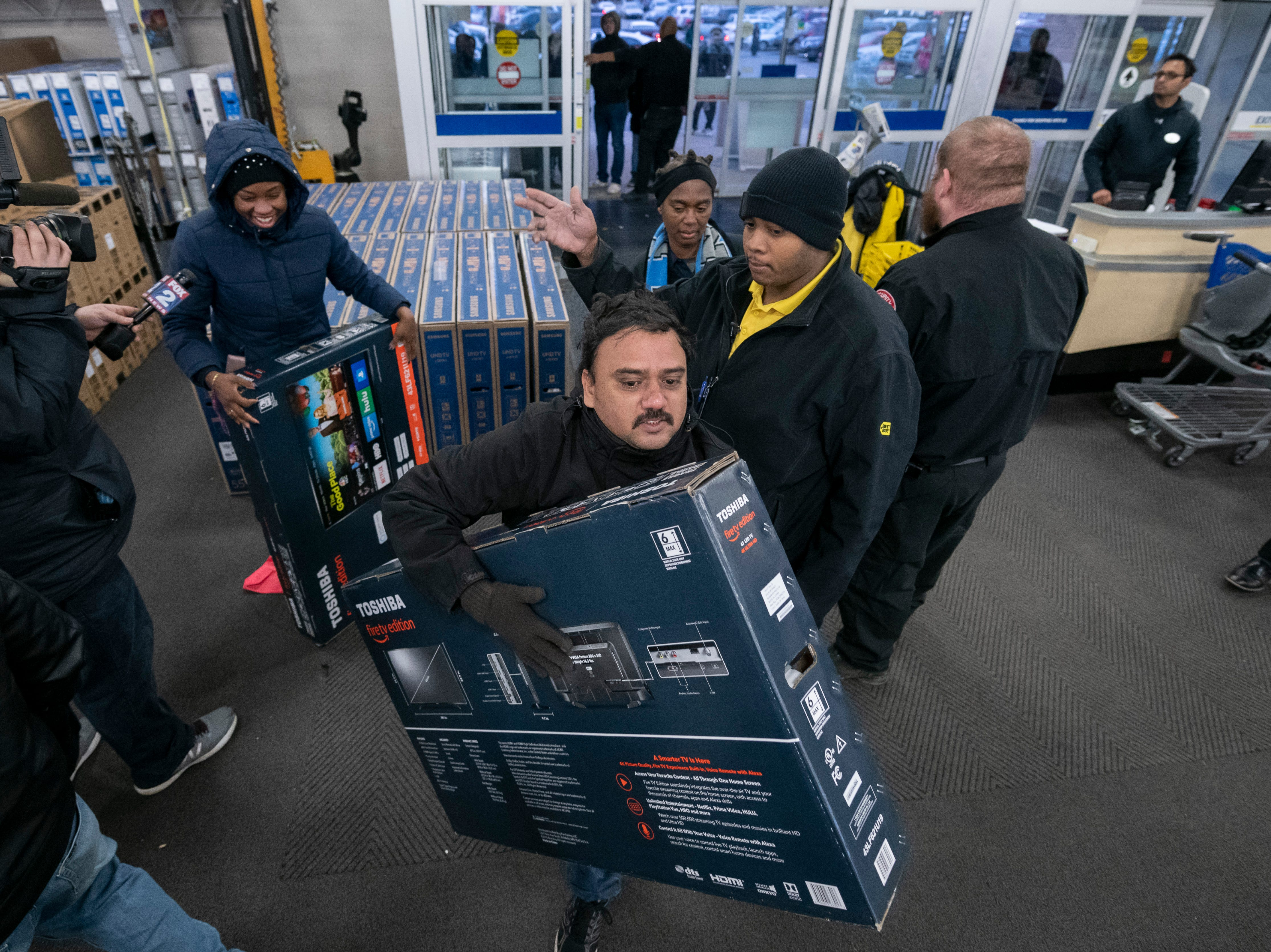 Shoppers grab televisions on sale.