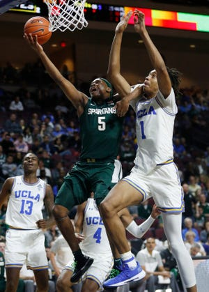 Michigan State's Cassius Winston (5) shoots next to UCLA's Moses Brown during the second half.