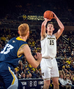 Michigan center Jon Teske attempts a jump shot while defended by Chattanooga center Thomas Smallwood.