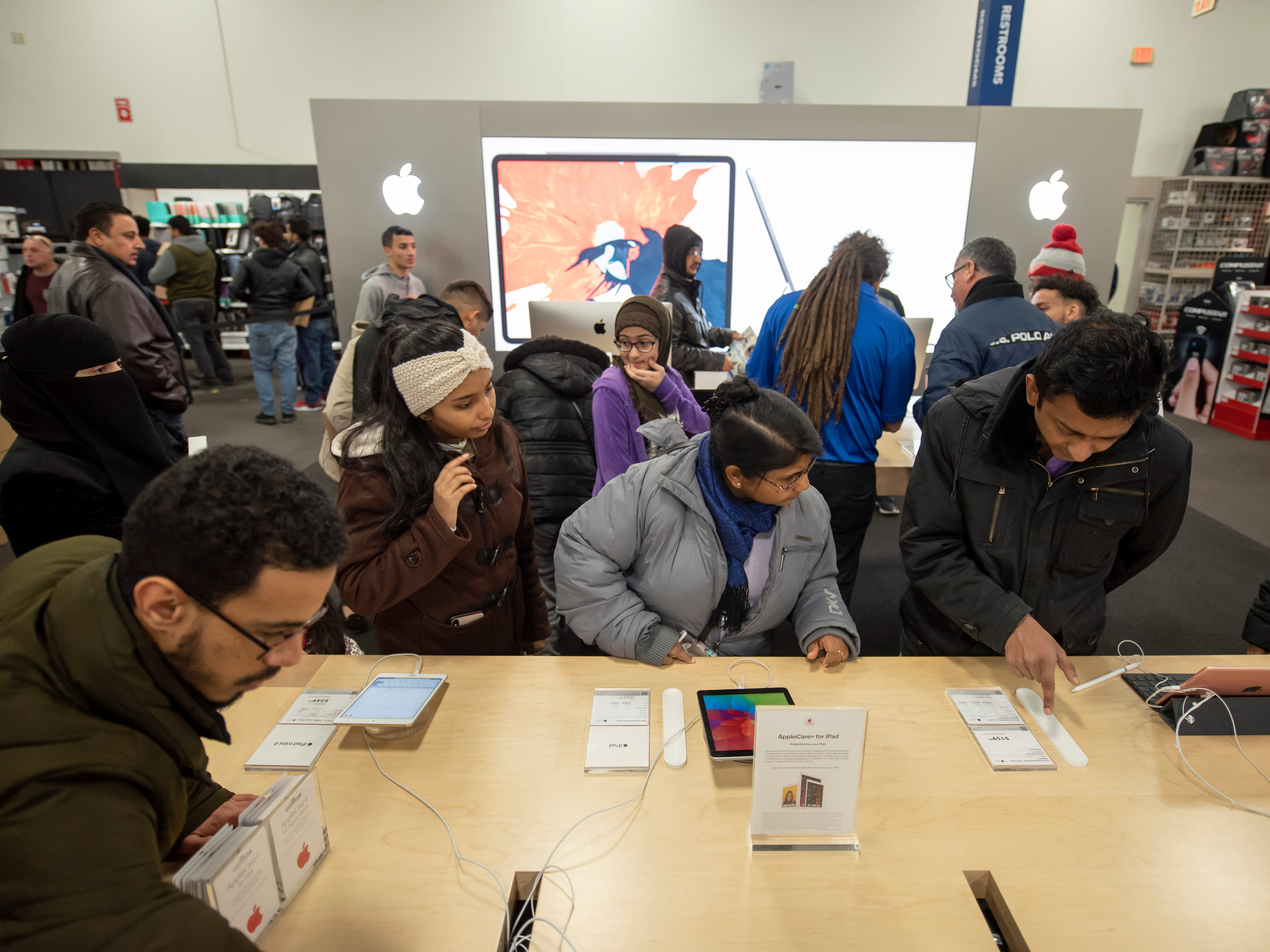 Shoppers look at Apple products during a Thanksgiving evening sale at Best Buy.