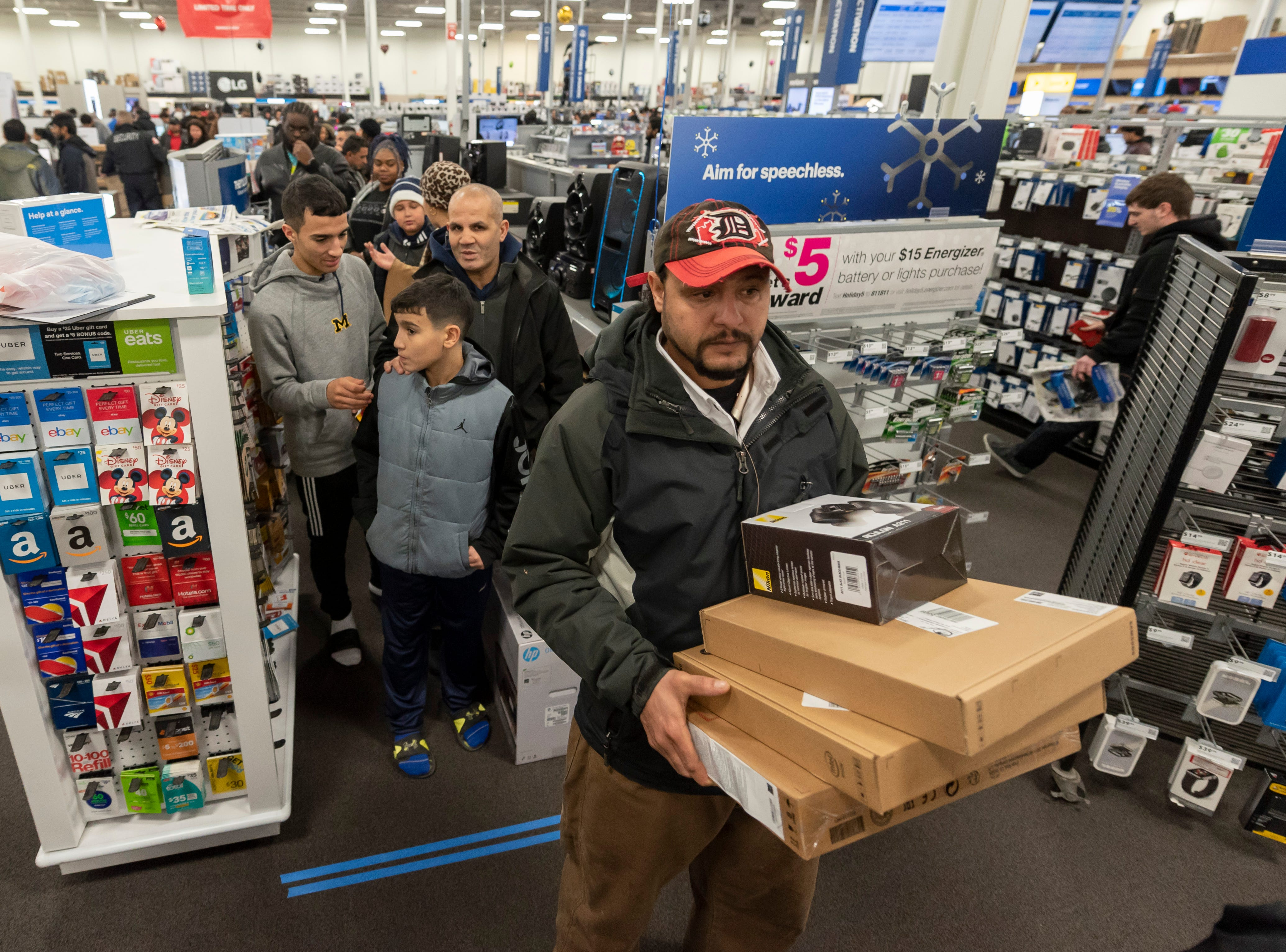 Shoppers wait in line to pay for merchandise during a Thanksgiving evening sale at Best Buy.
