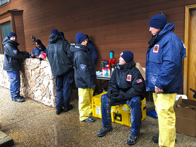 National Urban Search & Rescue Response System Orange County CATF-5 team members Imelda Cordova, third from right, talks Andrew Ricker, and Craig Stevens, far right, as their team take cover from the rain in Paradise, Calif., Friday, Nov. 23, 2018.