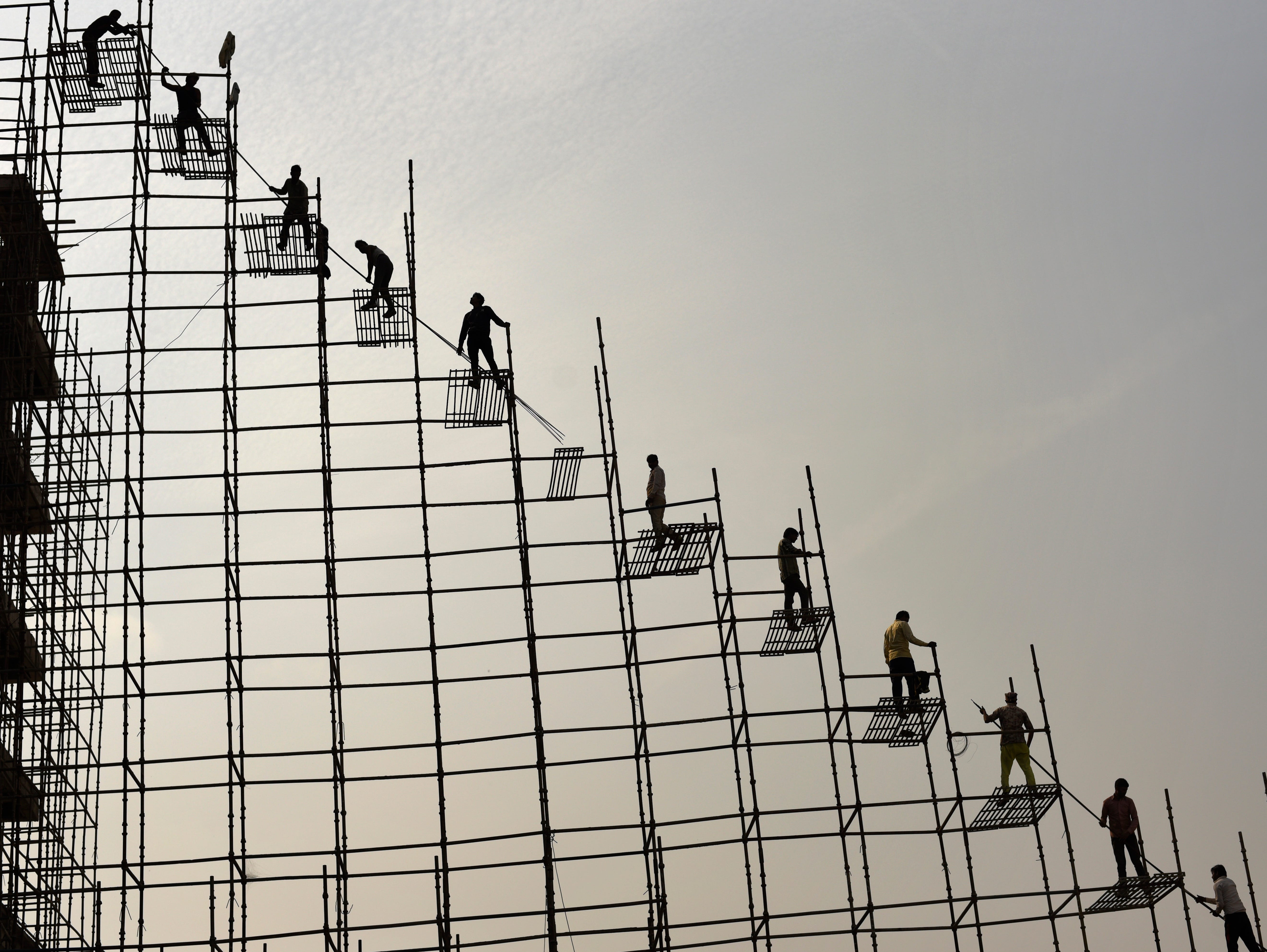 Indian laborers standing on scaffolding shift steel rods from the ground to the top of an under construction hospital building in Greater Noida, near New Delhi, India, Thursday, Nov. 22, 2018. Building work in the capital region has resumed after authorities last week lifted a ban on construction activities they had imposed to combat air pollution.
