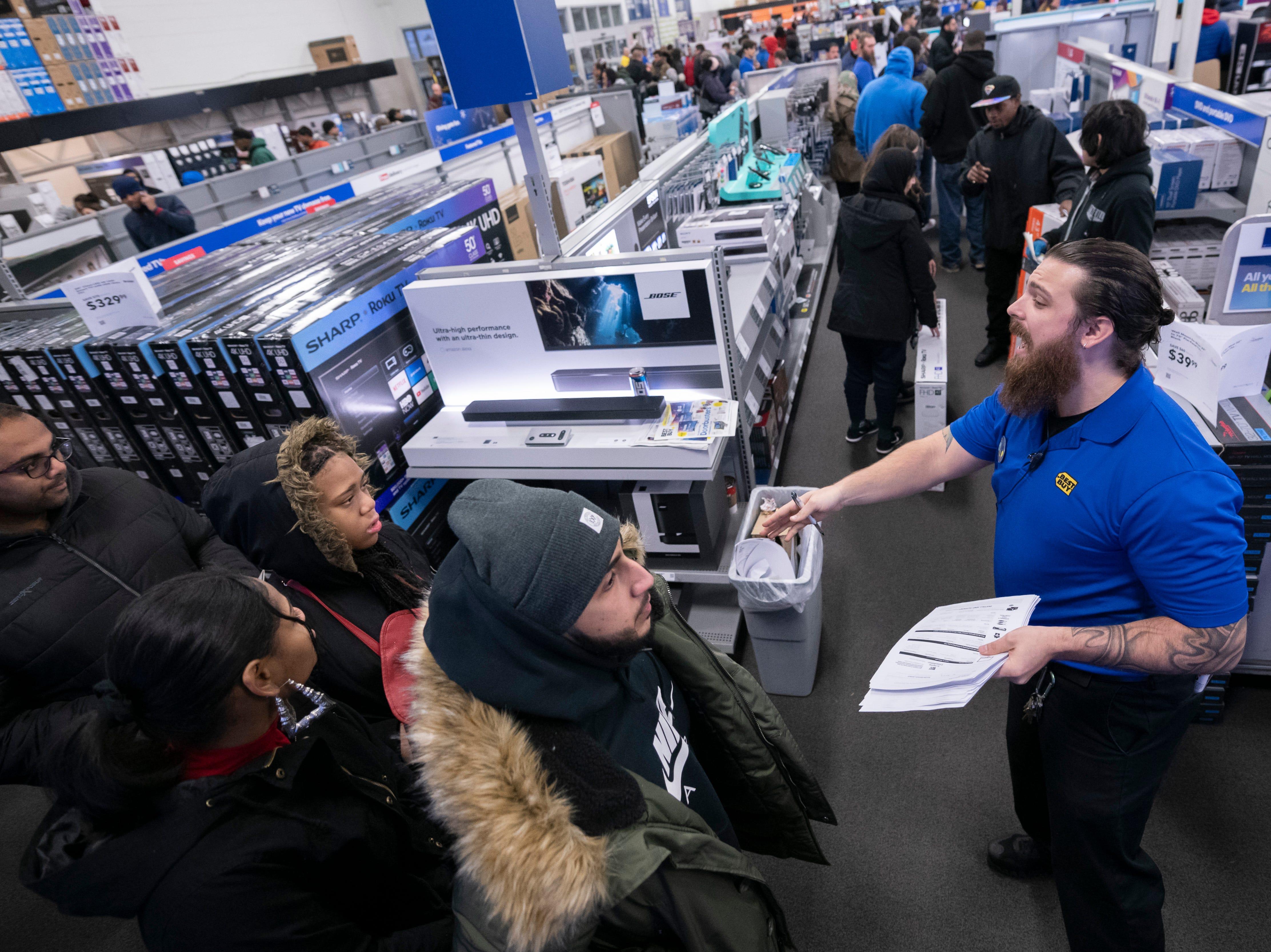 A sales clerk helps customers at Best Buy.