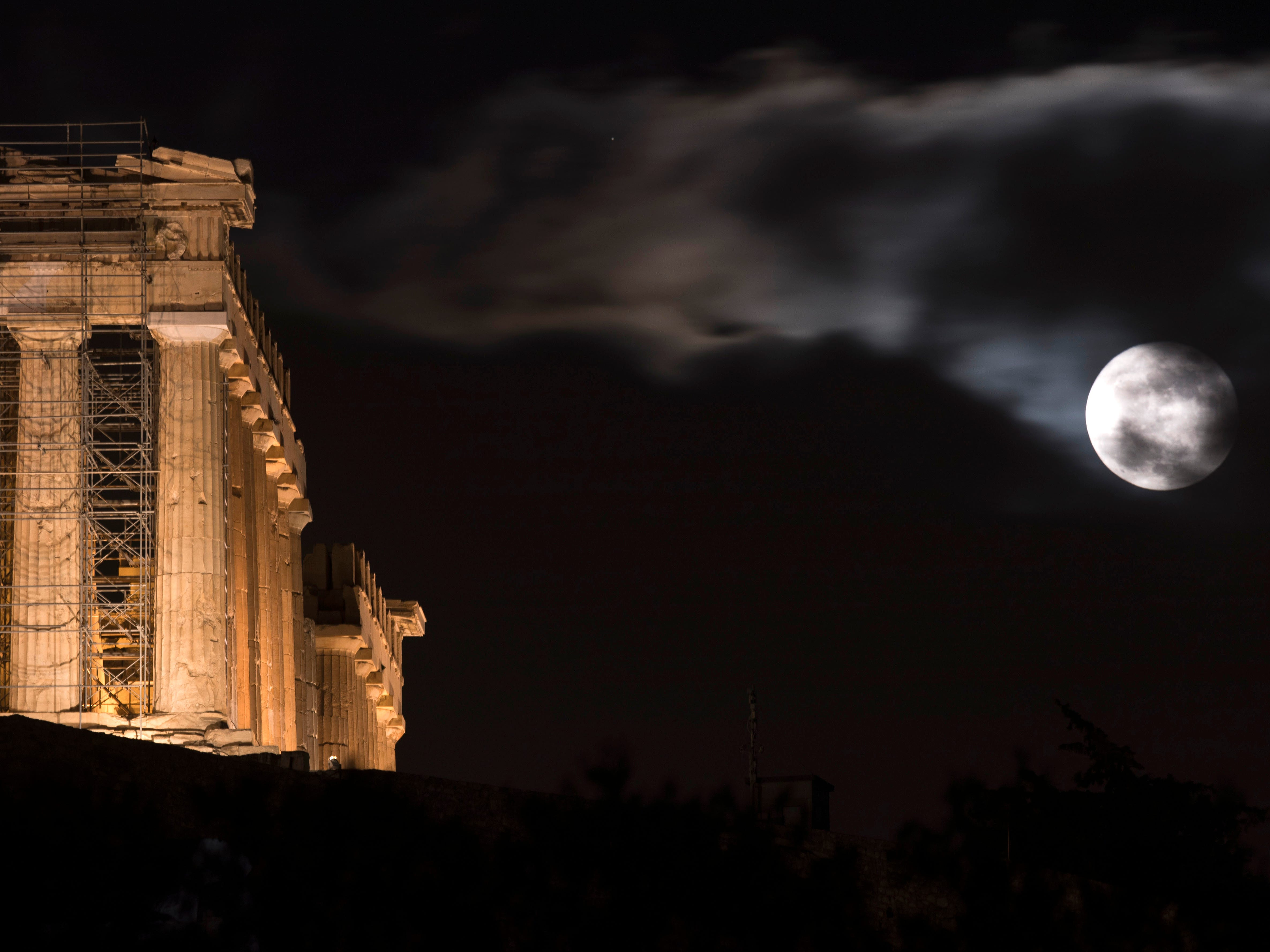 The full moon rises behind the 2,500-year-old Parthenon temple on the Acropolis of Athens on Friday, Nov. 23, 2018.