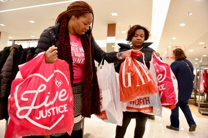 Sheena King, left, of Livonia, with her sister Kyla King, bag their early morning shopping deals at Twelve Oaks Mall in Novi Friday.