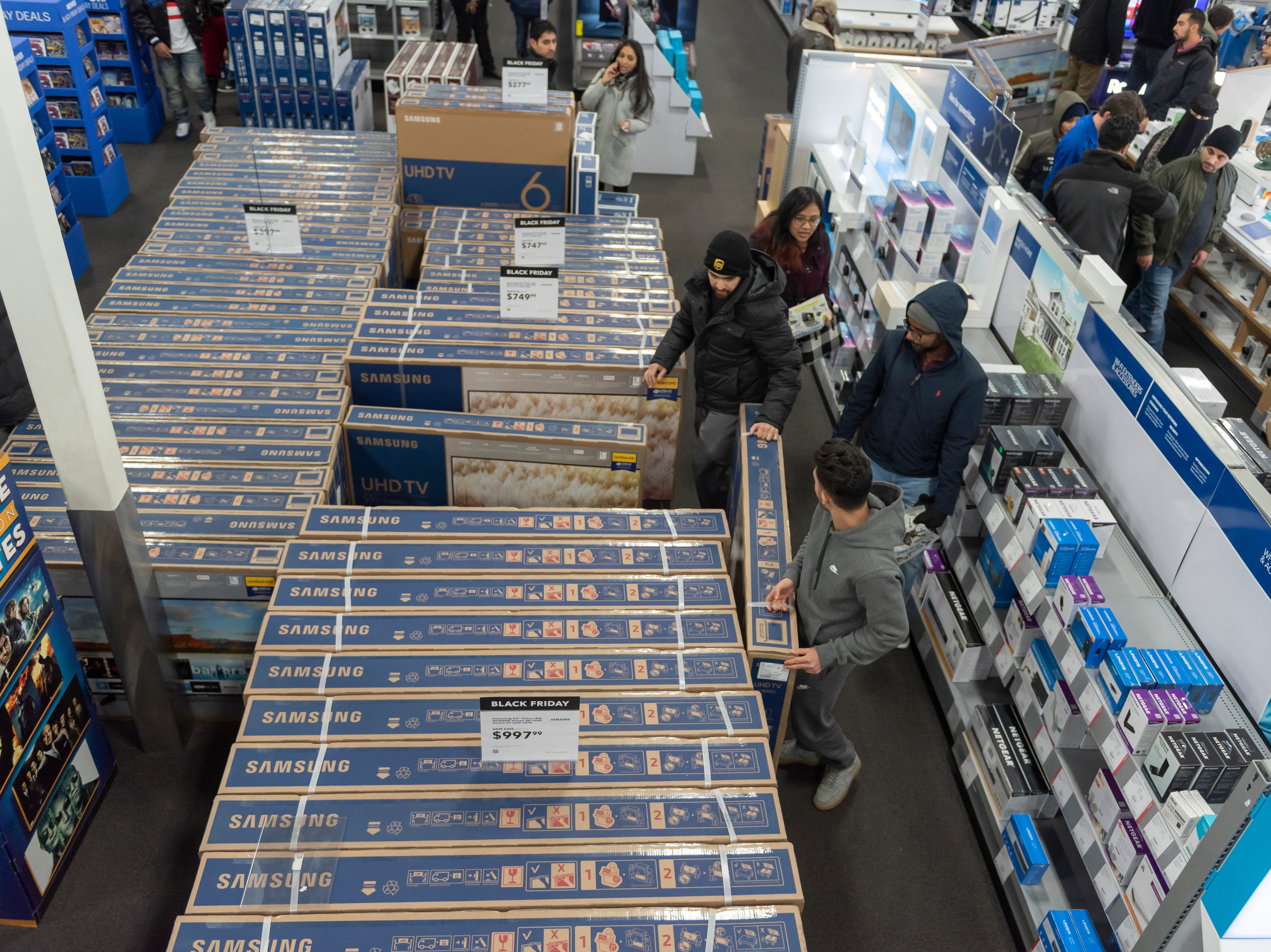 Shoppers look for merchandise during a Thanksgiving evening sale at Best Buy.