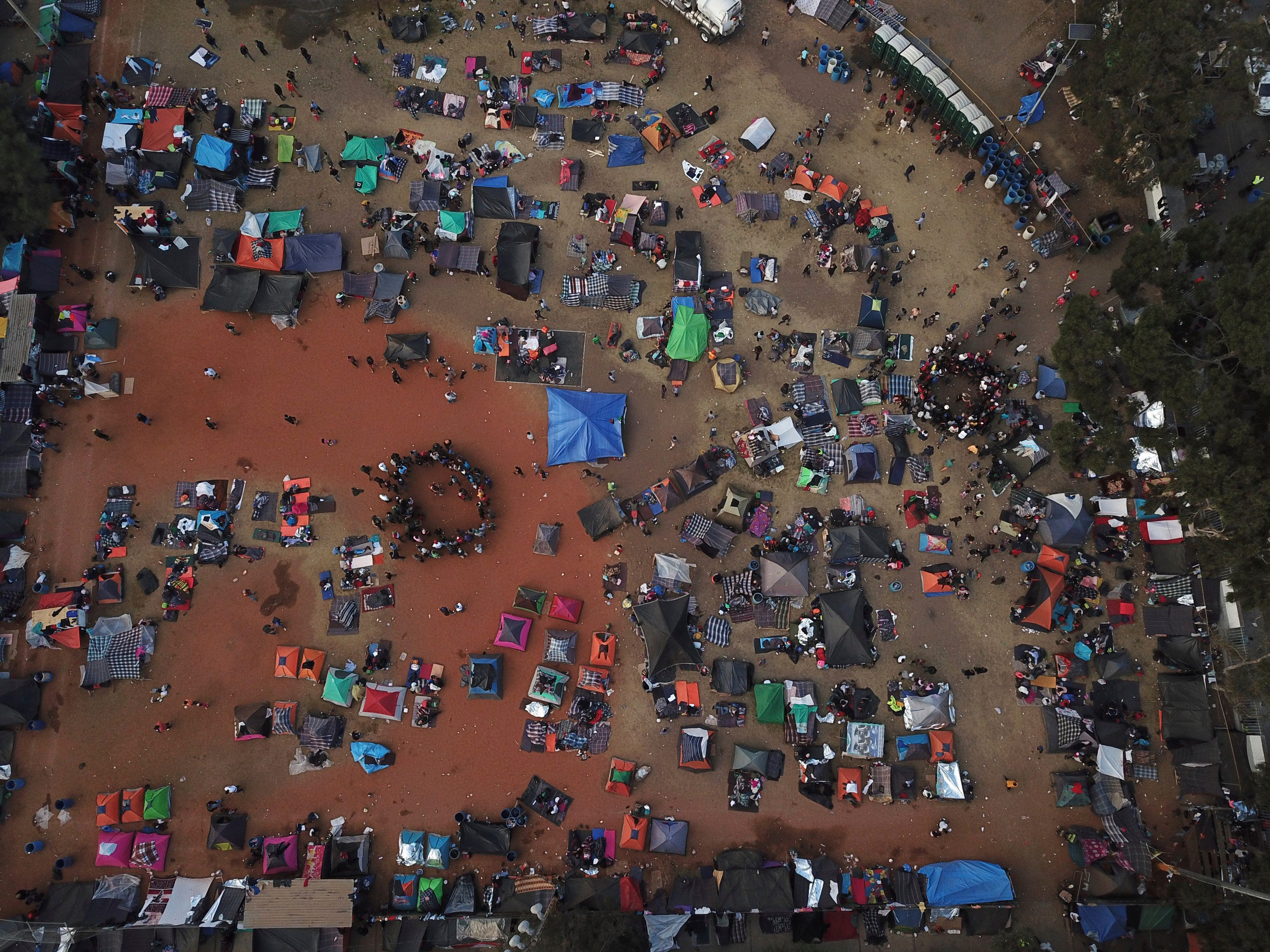 Central American migrants gather in an area designated for them to set up their tents in Tijuana, Mexico, Wednesday, Nov. 21, 2018. Migrants camped in Tijuana after traveling in a caravan to reach the U.S are weighing their options after a U.S. court blocked President Donald Trump's asylum ban for illegal border crossers.