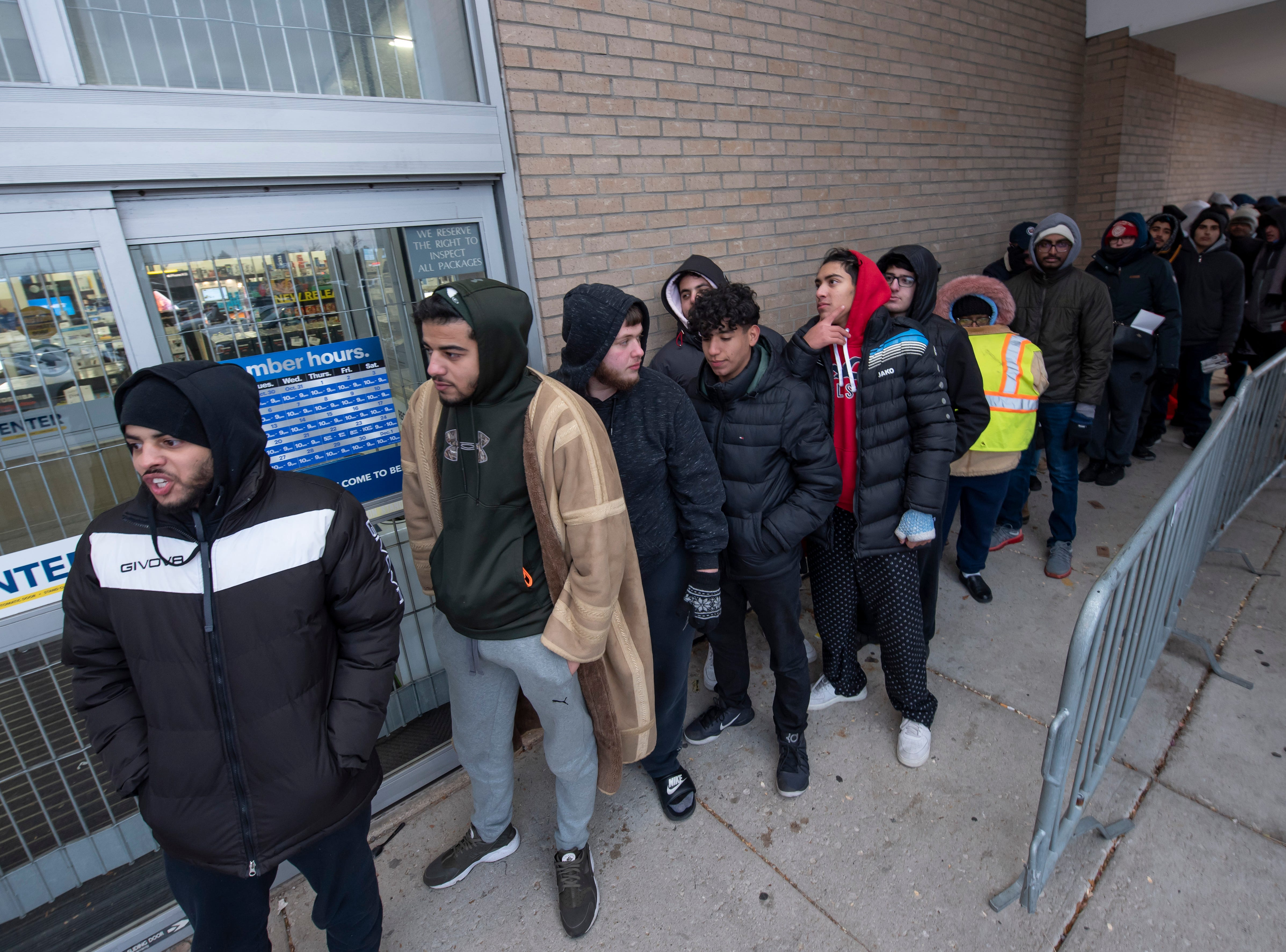 Shoppers wait outside in the cold to get into Best Buy in Dearborn.