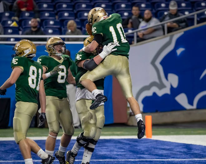 Lumen Christi's Nick Thomas (10) scores a touchdown in the first half and celebrates with teammates.