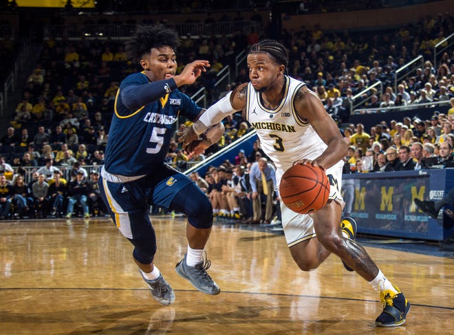 Chattanooga guard Donovann Toatley (5) defends against Michigan guard Zavier Simpson (3) in the first half.