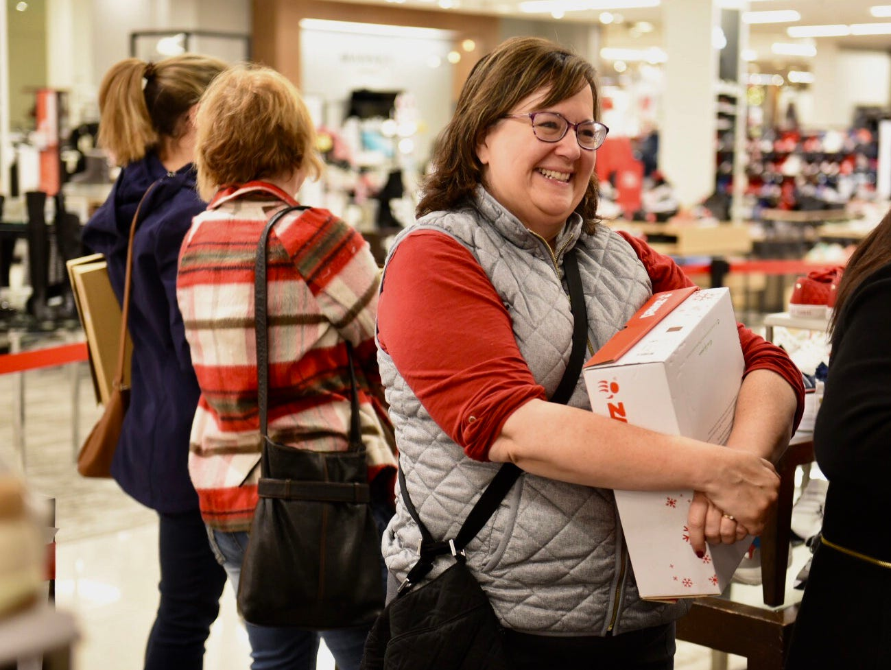 Shelia Breen of Livonia smiles as she waits in line at Macy's on Black Friday for their door buster sales at Twelve Oaks Mall in Novi.