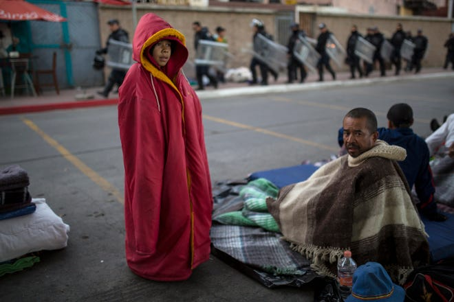 Jonathan Torres, 11, stands next to his father after waking up early in the morning as Mexican riot police make their way to the Chaparral border crossing, in Tijuana, Mexico, Friday, Nov. 23, 2018.