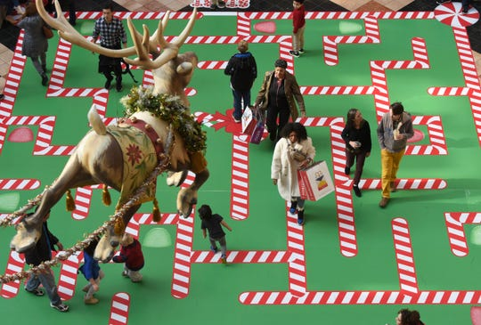 Shoppers maneuver through a candy cane maze at the Somerset Collection in Troy on Friday.