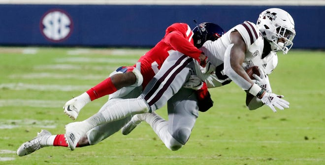 Mississippi State tight end Farrod Green (82) pulls in a pass reception against Mississippi defensive back Zedrick Woods during the first half on Thursday.
