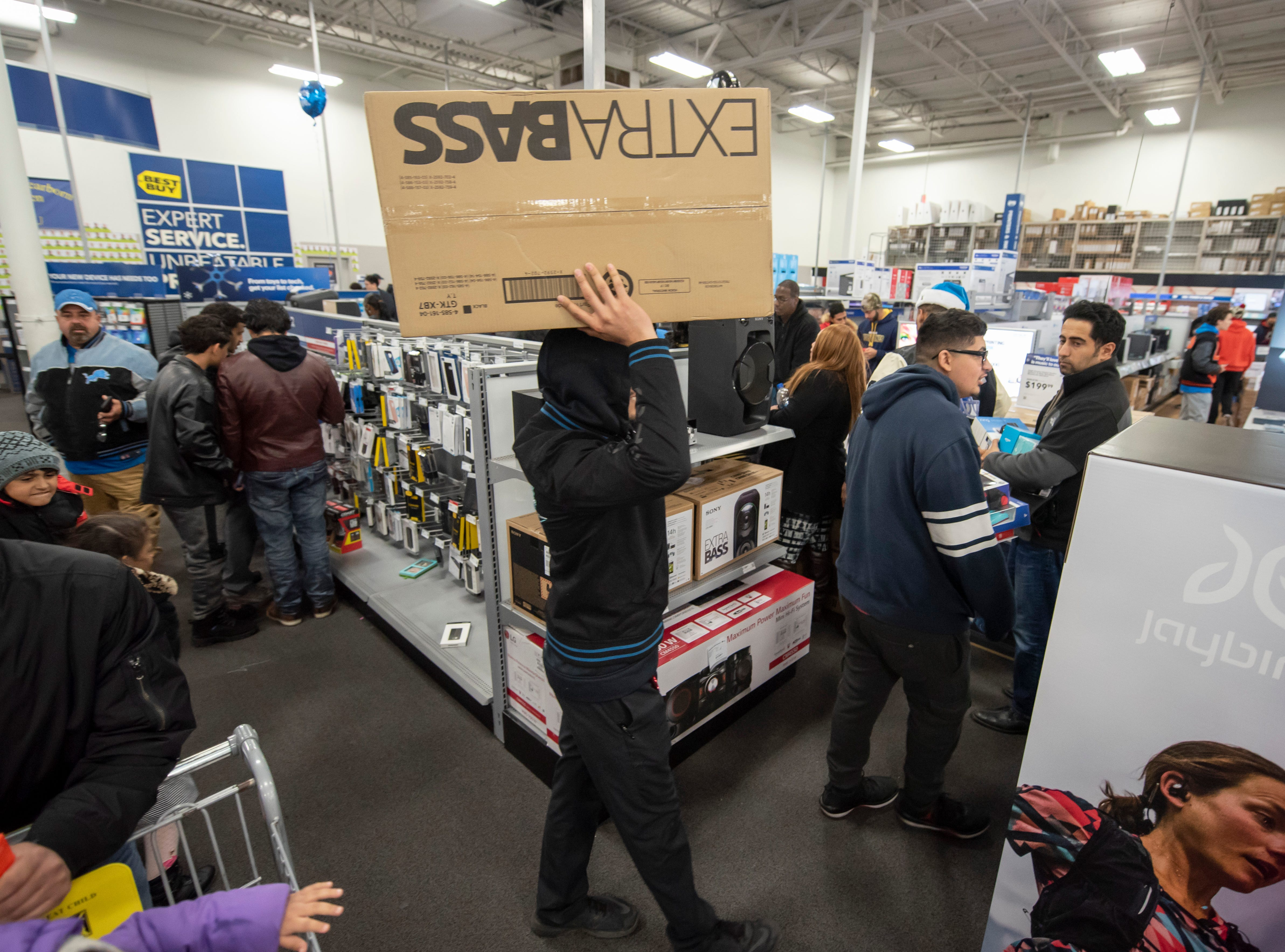 Shoppers carry merchandise during a Thanksgiving evening sale at Best Buy in Dearborn.