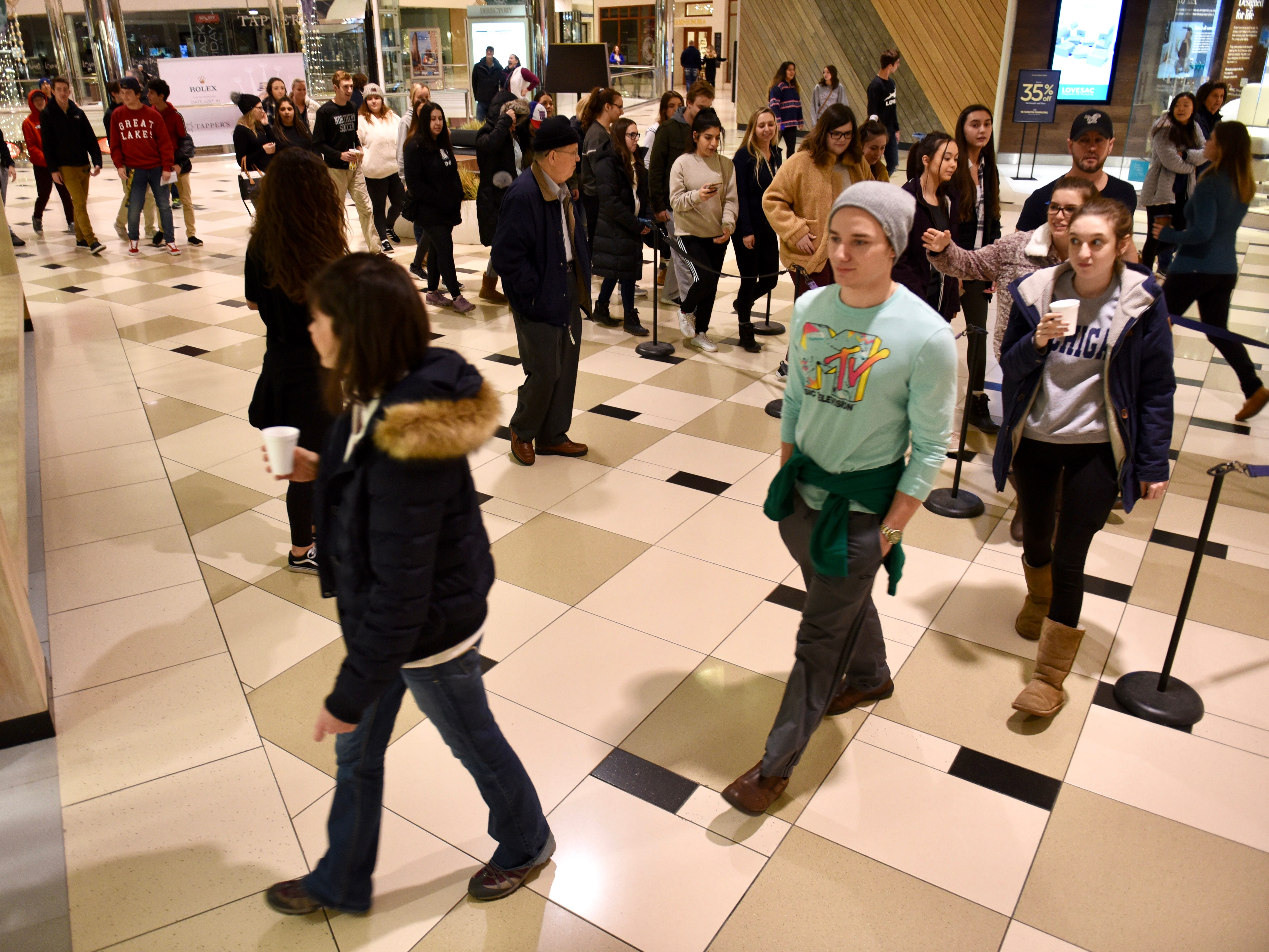 A line of shoppers, some with morning beverages in hand, enters the Lululemon store as doors open at Twelve Oaks Mall in Novi on Friday.