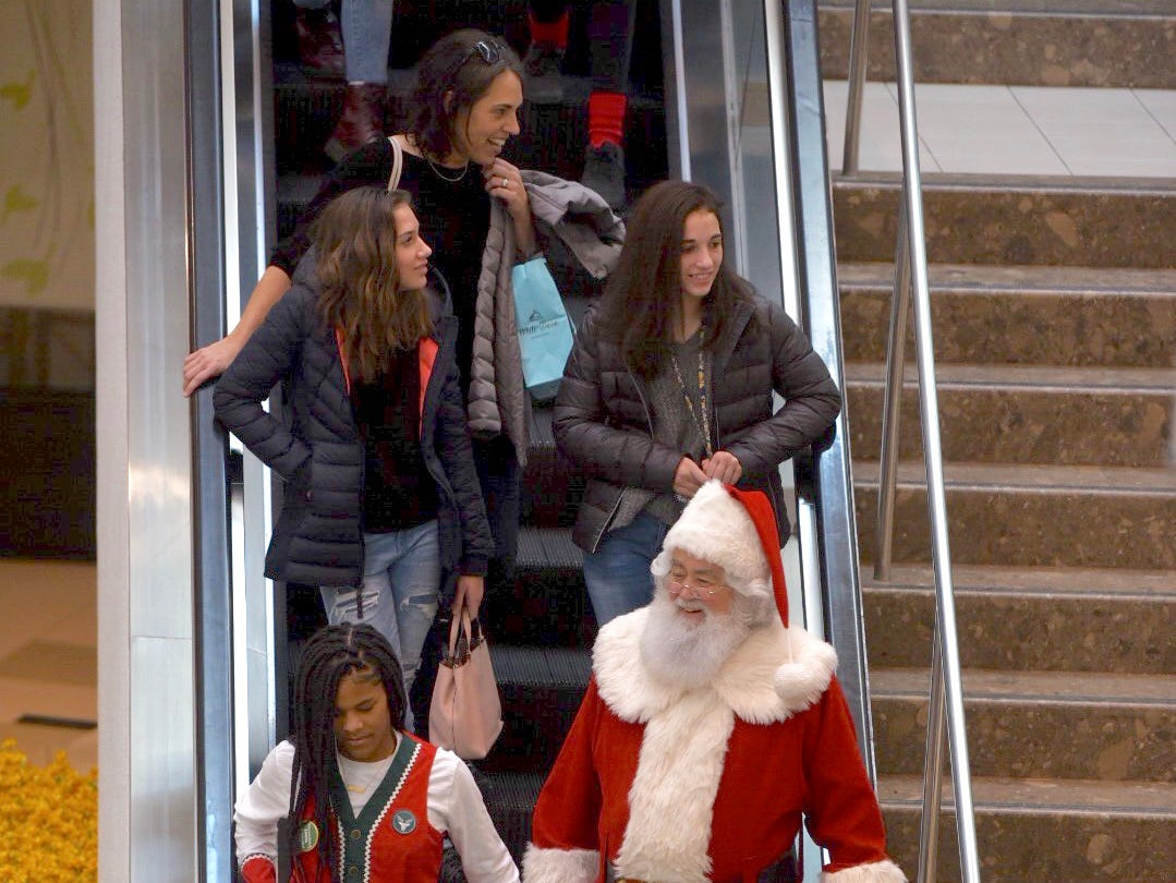 Santa Claus rides the escalator, seemingly unnoticed,  as he heads toward his winter wonderland to greet his fans at Twelve Oaks Mall in Novi, Friday.