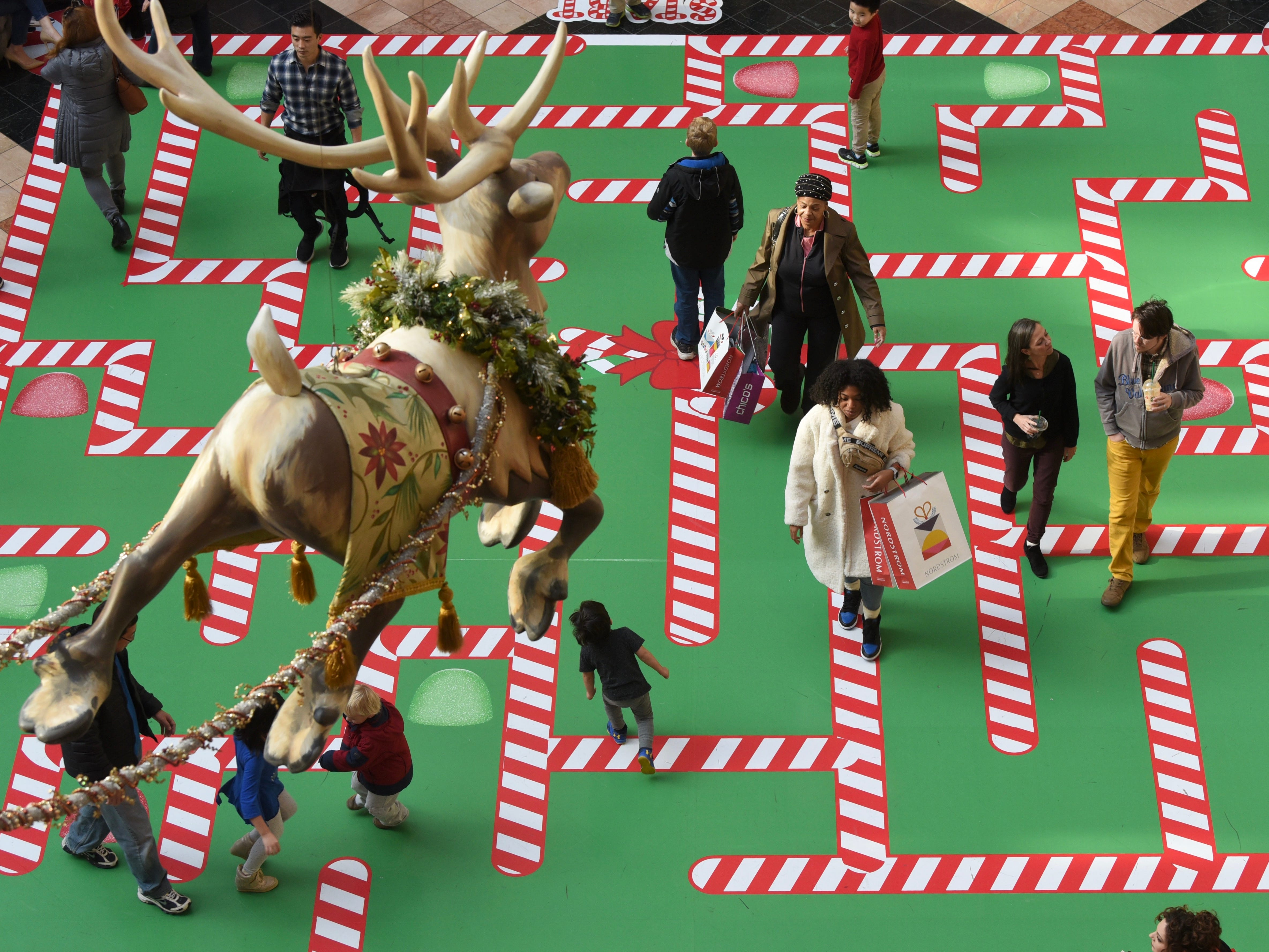 Black Friday shoppers maneuver through a candy cane maze at the Somerset Collection in Troy on Friday, November 23, 2018.