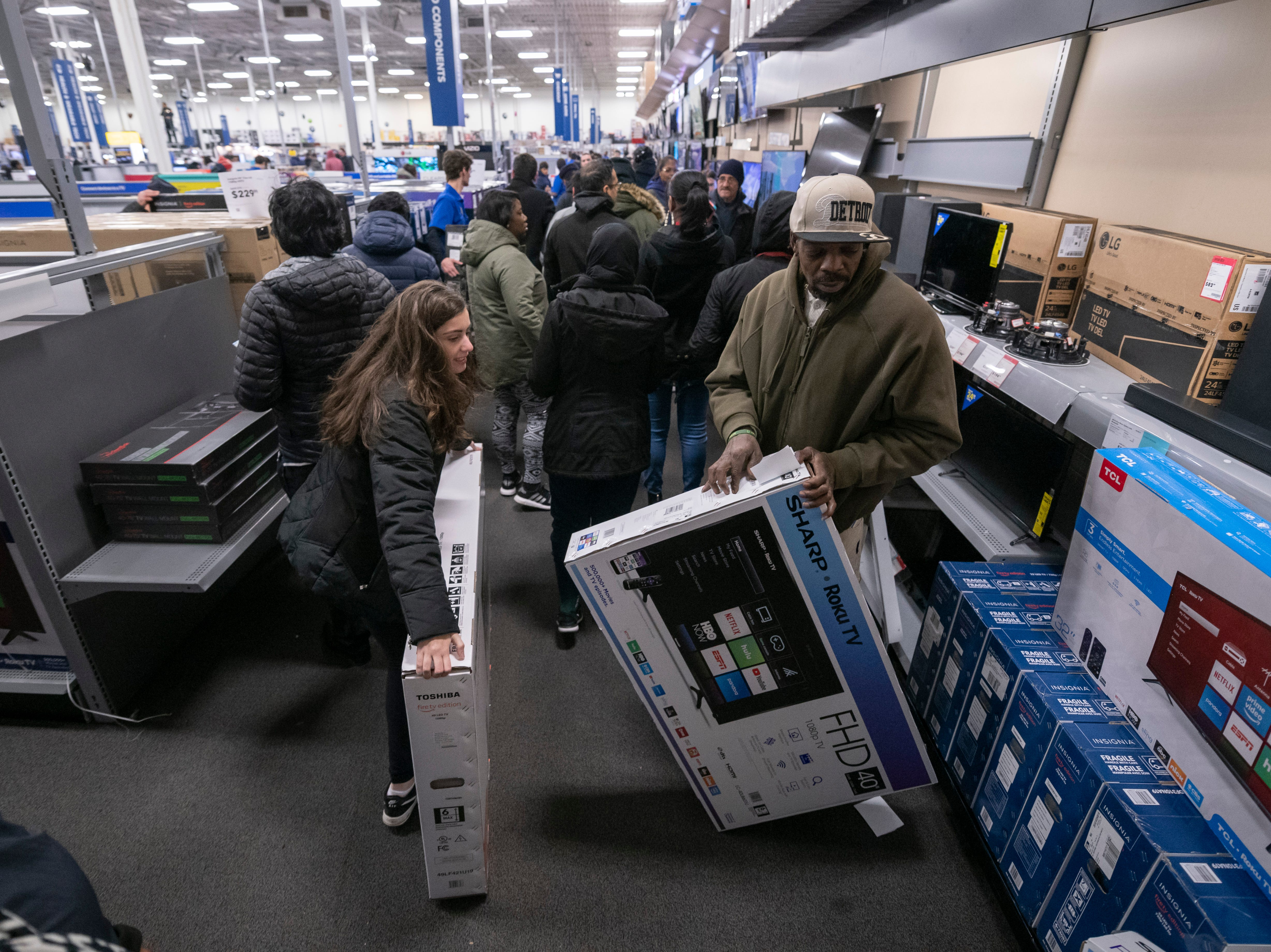 Shoppers grab televisions on sale at Best Buy in Dearborn.