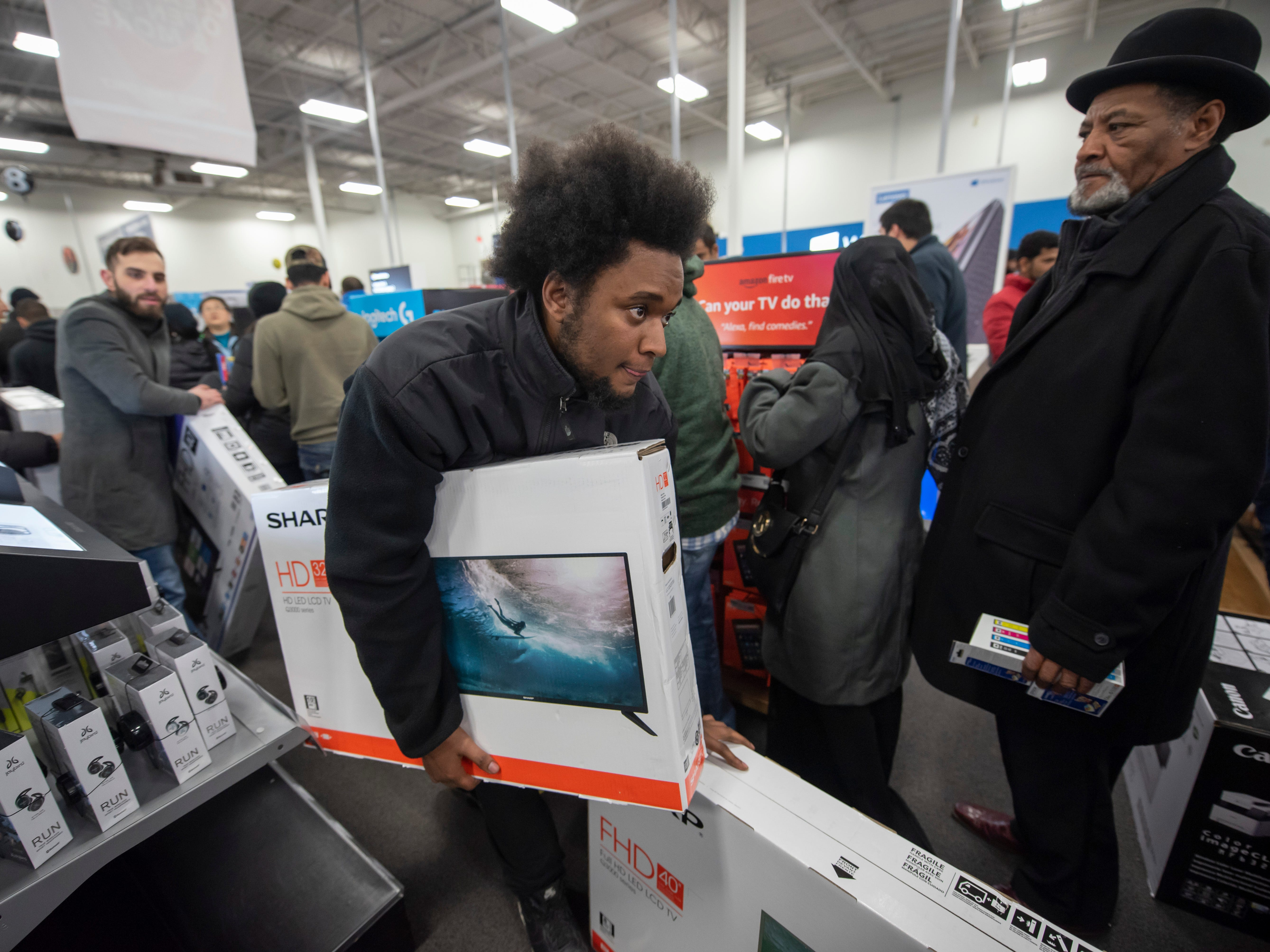 Justin Burton of Detroit carries two televisions sets while shopping during a Thanksgiving evening sale at Best Buy in Dearborn.
