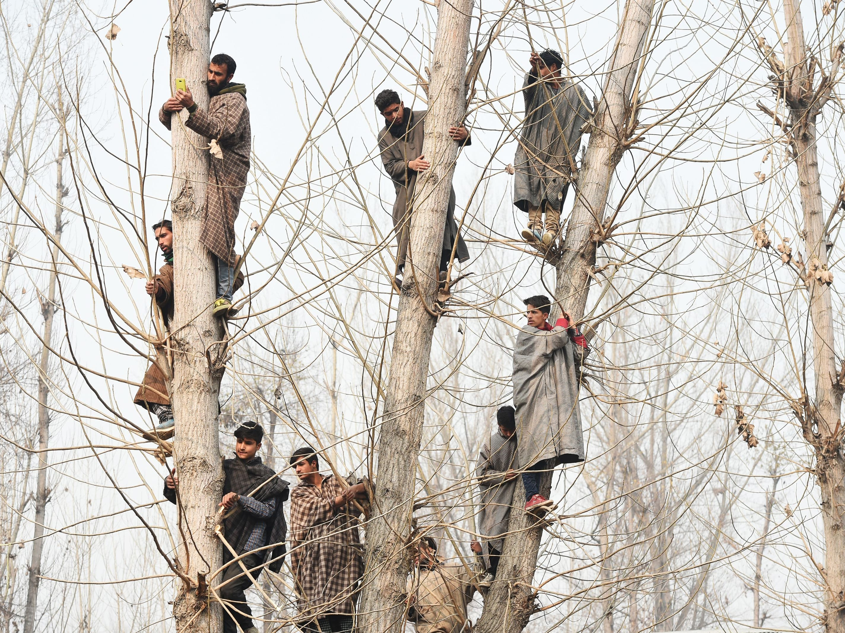 Kashmiri villagers look on from atop a tree during the funeral procession of militant Azad Ahmed Malik, who was killed in a gun battle with Indian soldiers, in Arwani village in Kashmir on Friday, November 23, 2018. - Six militants were killed during a gun battle with Indian governments forces early in the morning.