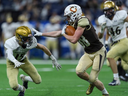 Central's Brennan Schutte (38) pushes past Bishop Dwenger's Howard Steele (15) during the IHSAA Class 4A state championship game at Lucas Oil Stadium in Indianapolis, Ind., Friday, Nov. 23, 2018.