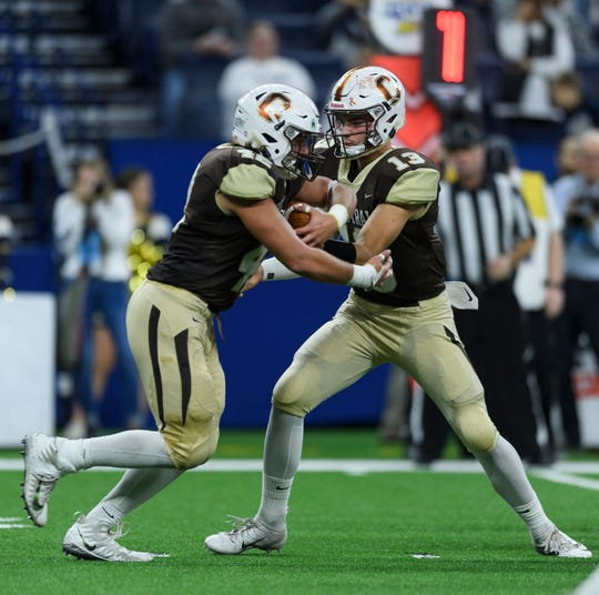 Central's Brennon Harper (13) hands-off the ball to Central's Austin Frasier (42) during the IHSAA Class 4A state championship against the Fort Wayne Bishop Dwenger Saints at Lucas Oil Stadium in Indianapolis, Ind., Friday, Nov. 23, 2018.