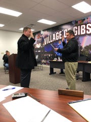 Gibsonburg Mayor Steve Fought, right, swears in new assistant police chief Don Karr Tuesday.